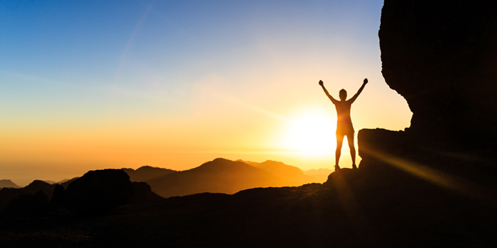 Woman achieving financial goals on top of mountain