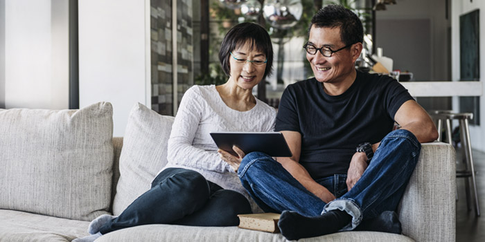 Couple sitting on the couch reading how they can get their stimulus check faster