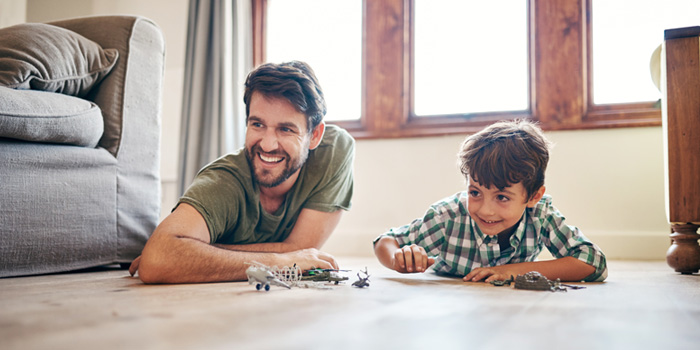 Father and son playing with toys inside