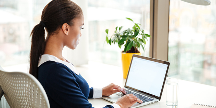 Woman on her computer researching how the CARES Act impacts her student loans