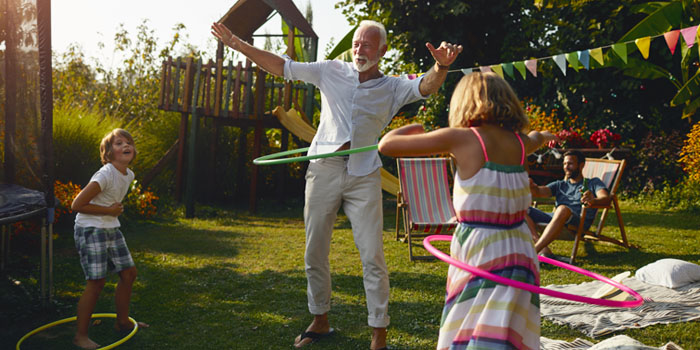Grandfather playing outside with his grandchildren