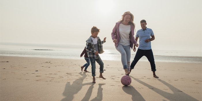 Family playing soccer on the beach