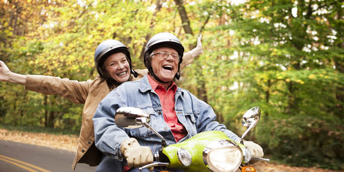 Couple on the back of a scooter driving in a wooded area enjoying their retirement