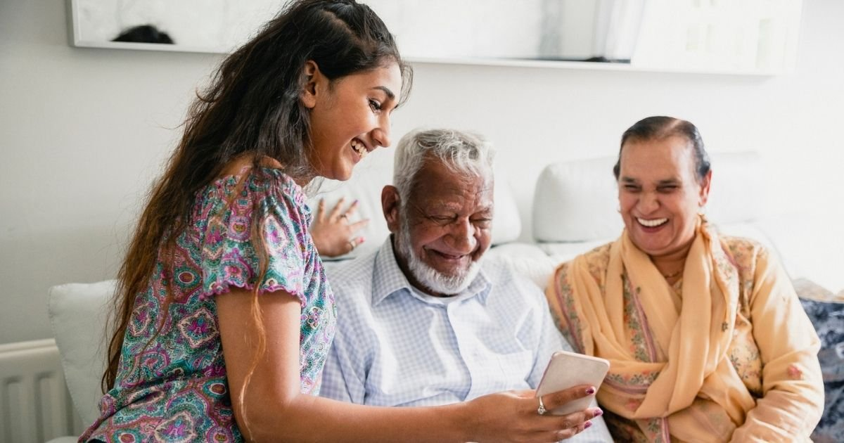 Girl showing her grandparents something on her phone